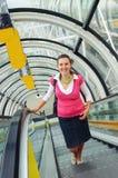 La mujer feliz joven se levanta en la escalera móvil Imagenes de archivo