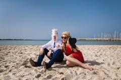 La mujer feliz joven se sienta con el hombre de negocios en máscara divertida Foto de archivo