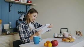 La mujer feliz joven sorprendió recibir la letra de la lectura de las buenas noticias en la cocina mientras que desayune en casa  metrajes