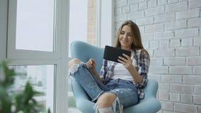 La mujer feliz joven tiene charla video en línea usando la tableta digital que se sienta en balcón en el apartamento moderno del  metrajes