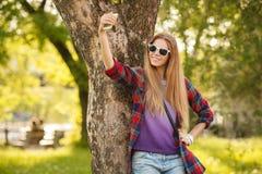 La mujer feliz joven toma el selfie en el teléfono celular en parque de la ciudad del verano Muchacha moderna hermosa en gafas de Imagen de archivo libre de regalías