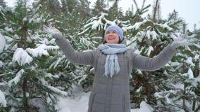 La mujer feliz lanza nieve en el aire en bosque del pino el día de invierno almacen de metraje de vídeo