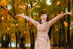 La mujer feliz lanza para arriba las hojas de otoño para arriba Fotos de archivo libres de regalías