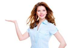 La mujer feliz lleva a cabo algo en la palma Imagenes de archivo
