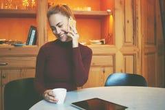 La mujer feliz magnífica está hablando en el teléfono de célula mientras que está bebiendo té en cafetería moderna Imágenes de archivo libres de regalías