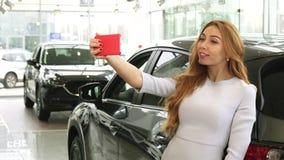 La mujer feliz magnífica que toma selfies acerca a su nuevo coche en la representación metrajes