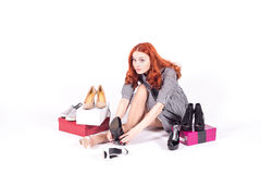 La mujer feliz mide el gran número de pares de zapatos Imágenes de archivo libres de regalías