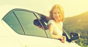 La mujer feliz mira hacia fuera la ventanilla del coche en la naturaleza Imágenes de archivo libres de regalías