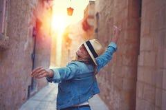La mujer feliz que camina encendido mediterreanen la calle en puesta del sol fotografía de archivo