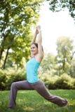 La mujer feliz que hace ejercicios de la yoga, medita en el parque Fotos de archivo libres de regalías