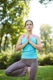 La mujer feliz que hace ejercicios de la yoga, medita en el parque Fotos de archivo