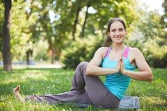 La mujer feliz que hace ejercicios de la yoga, medita en el parque Imagenes de archivo