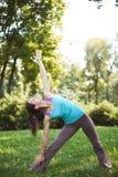 La mujer feliz que hace ejercicios de la yoga, medita en el parque Imagen de archivo libre de regalías