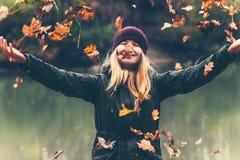 La mujer feliz que jugaba con las hojas de otoño aumentó las manos Fotos de archivo