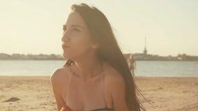 La mujer feliz que se sentaba en una playa de la arena en verano hizo excursionismo en el resplandor de oro de la sol de la puest metrajes