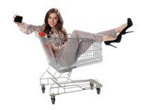 La mujer feliz que se sienta en carretilla de las compras y se hace la foto Fotos de archivo