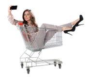 La mujer feliz que se sienta en carretilla de las compras y se hace la foto Foto de archivo