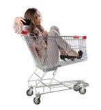 La mujer feliz que se sienta en carretilla de las compras y se hace la foto Fotografía de archivo libre de regalías