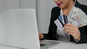 La mujer feliz que sostiene dólares de EE. UU. y tarjetas de crédito acerca a su ordenador portátil Foto de archivo libre de regalías