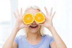 La mujer feliz que tiene cubierta de la diversión observa con la naranja Fotos de archivo libres de regalías