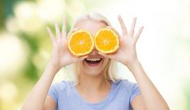 La mujer feliz que tiene cubierta de la diversión observa con la naranja Foto de archivo libre de regalías