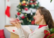La mujer feliz recibió el paquete con el regalo de la Navidad Fotografía de archivo libre de regalías