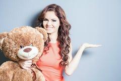 La mujer feliz recibió un oso de peluche en la celebración Foto de archivo