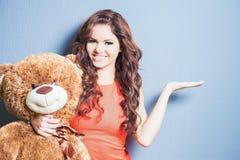La mujer feliz recibió un oso de peluche en la celebración Fotos de archivo libres de regalías