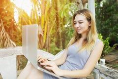 La mujer feliz rubia utiliza el ordenador de la PC para el trabajo el día soleado, fondo de las palmas del verde de la sol en via Foto de archivo libre de regalías