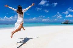 La mujer feliz salta del entusiasmo en una playa tropical imagenes de archivo