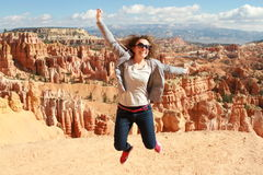 La mujer feliz salta en Bryce Canyon que mira y que disfruta de la visión fotografía de archivo