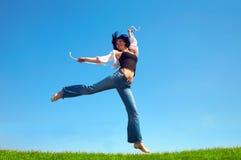 La mujer feliz salta en campo Foto de archivo libre de regalías