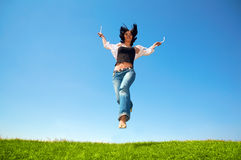 La mujer feliz salta en campo Fotografía de archivo libre de regalías