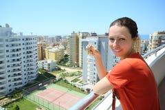 La mujer feliz se coloca en balcón Fotografía de archivo libre de regalías