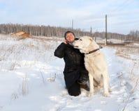 La mujer feliz se está sentando con un pastor asiático central en un camino rural del invierno contra el contexto del pueblo fotos de archivo libres de regalías