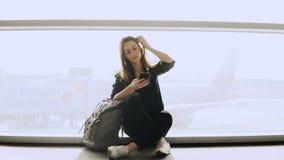La mujer feliz se sienta con smartphone por la ventana del aeropuerto Muchacha caucásica con la mochila usando el mensajero app e almacen de metraje de vídeo