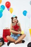 La mujer feliz se sienta en la posición de loto que sostiene la caja de regalo grande Foto de archivo