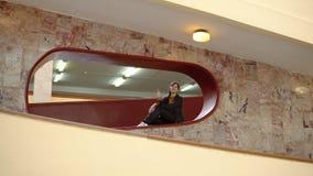 La mujer feliz se sienta en un lugar y muestra los pulgares para arriba dentro con las paredes de mármol metrajes