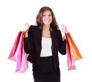 La mujer feliz se sostiene en ambos bolsos de manos con las compras Imagenes de archivo