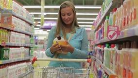 La mujer feliz selecciona las sustancias químicas de hogar en el supermercado almacen de video