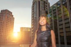 La mujer feliz sonríe y disfruta de la puesta del sol Imagen de archivo libre de regalías