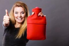 La mujer feliz sostiene la botella de agua caliente Foto de archivo libre de regalías