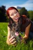 La mujer feliz sostiene el perro en parque Foto de archivo