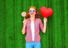 La mujer feliz sostiene un balón de aire rojo en la forma de un corazón, piruleta imágenes de archivo libres de regalías