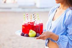 La mujer feliz sostiene un plato con un jugo rojo de las bebidas en la puesta del sol Picn foto de archivo libre de regalías