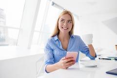 La mujer feliz toma un descanso para tomar café durante su trabajo foto de archivo