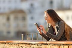 La mujer feliz utiliza un teléfono elegante en un balcón en la puesta del sol foto de archivo