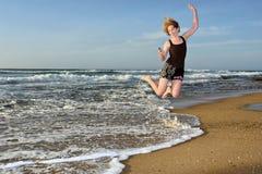 La mujer feliz vuela con con el teléfono móvil en la playa Imagen de archivo libre de regalías
