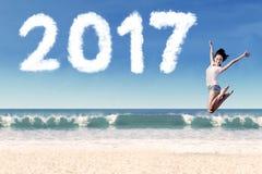 La mujer feliz y numera 2017 en la playa Imagen de archivo libre de regalías