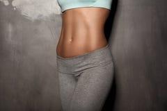 La mujer femenina de la aptitud con el cuerpo muscular, hace su entrenamiento, ABS, abdominals Foto de archivo